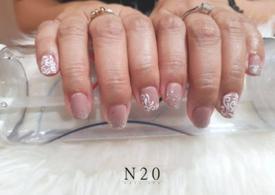 Patterned Nail Art: White Floral Swirls on Pink Manicure